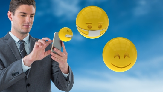 Digital composite of Businessman using smart phones while emojis
